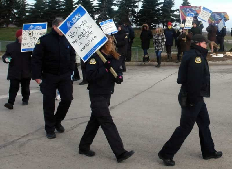 OPSEU members attend rally for corrections & hold up signs about having the right to a safe workplace