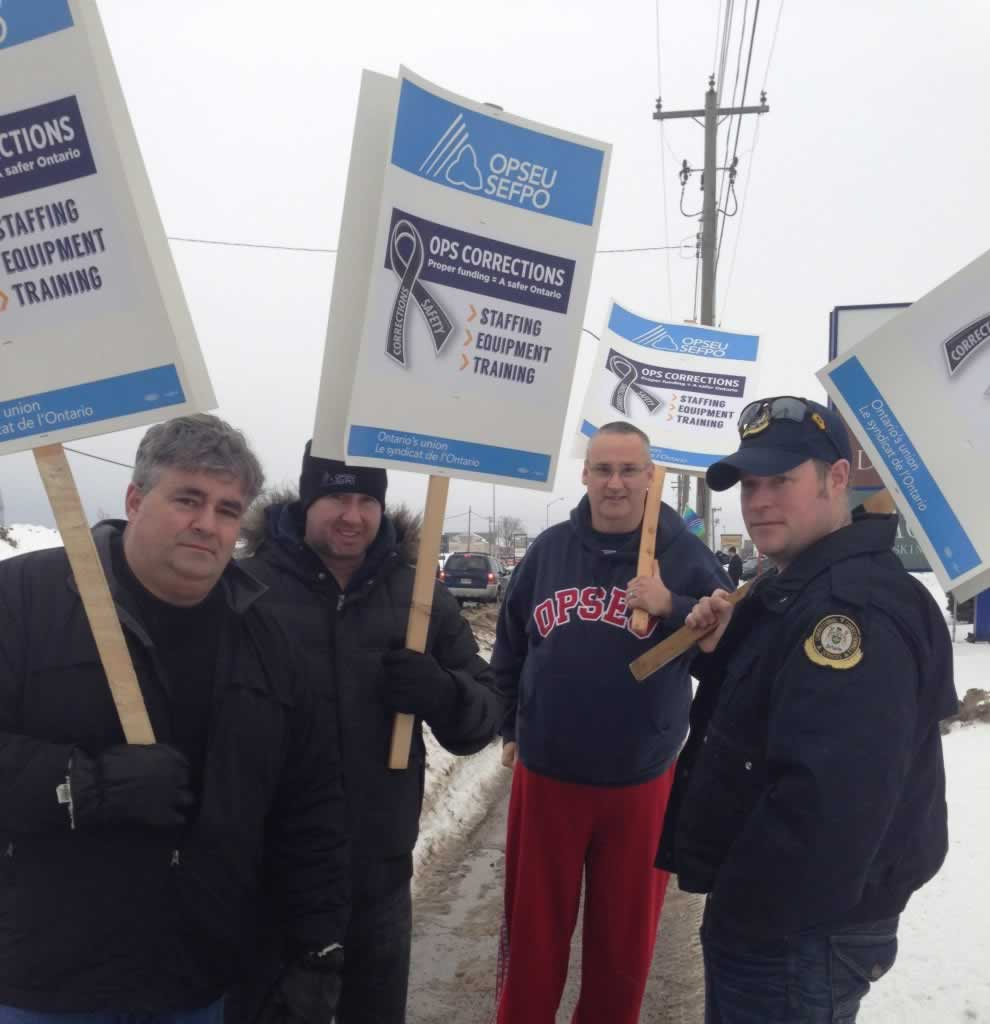 OPSEU members hold up signs as they attend rally for corrections in Sault Ste Marie