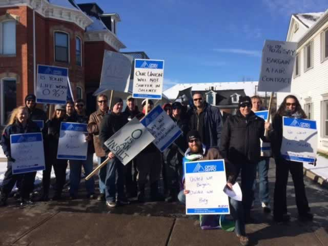 OPSEU members holding signs & flags as they attend rally in waterdown