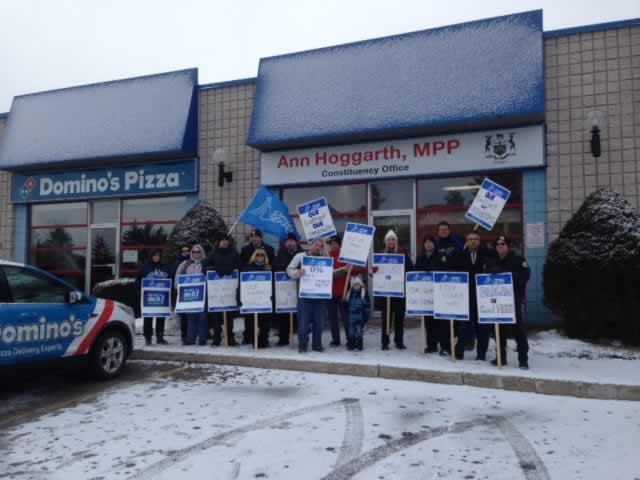 OPSEU members holding up signs outside of MPP Ann Hoggarth's office