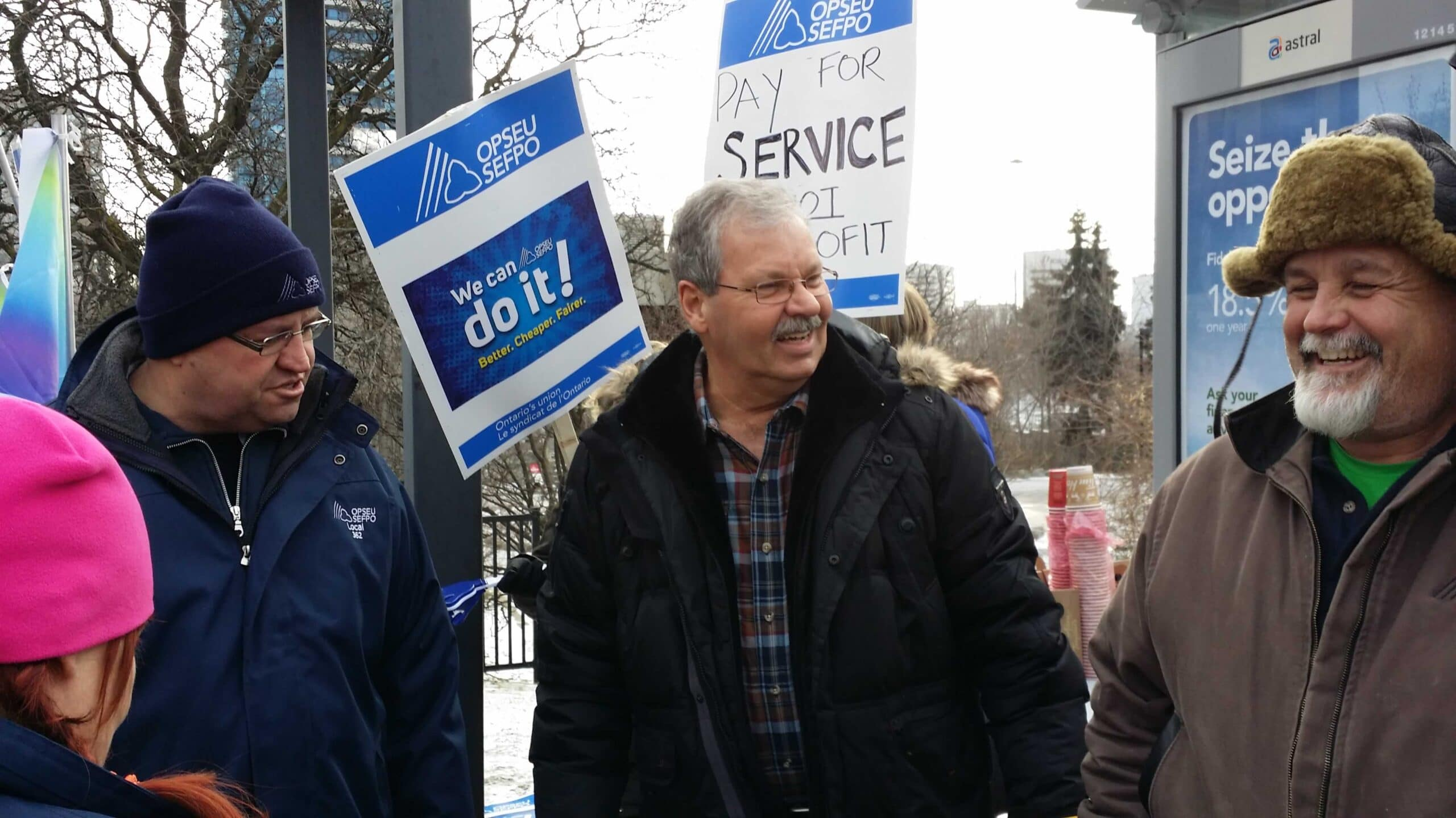 Smokey Thomas attends rally. Signs that say 'We can do it! Better. Cheaper. Fairer'