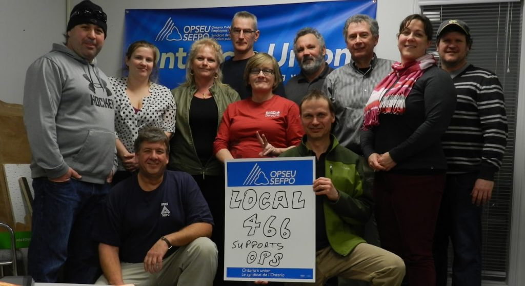 Brockville presidents pose together, holding up a sign that says: Local 466 supports OPS