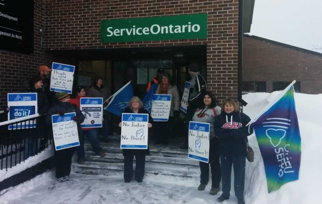 OPSEU members stand outside a Service Ontario with signs that say: No justice, No peace in Ignace