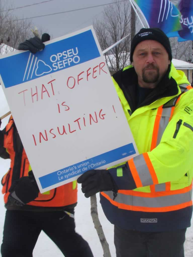 OPSEU member holds up a sign that says 'That Offer is Insulting!' in Chapleau