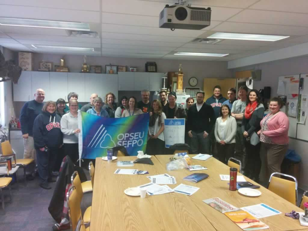 OPSEU members pose together, holding up a colourful OPSEU flag during the Sioux lookout