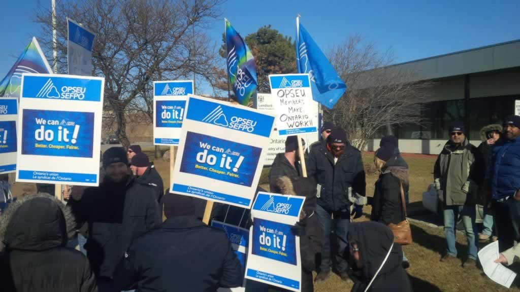 OPSEU members hold up signs as they attend rally in Midland Ave