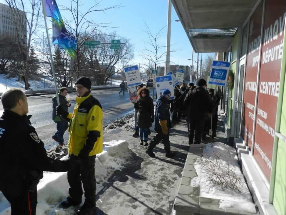 OPSEU members holding signs outside of Naqvi's office