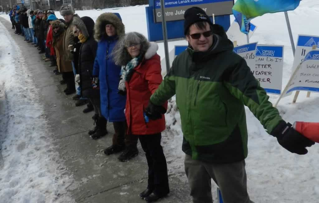 OPSEU members holding hands together in Centre Jules-Leger