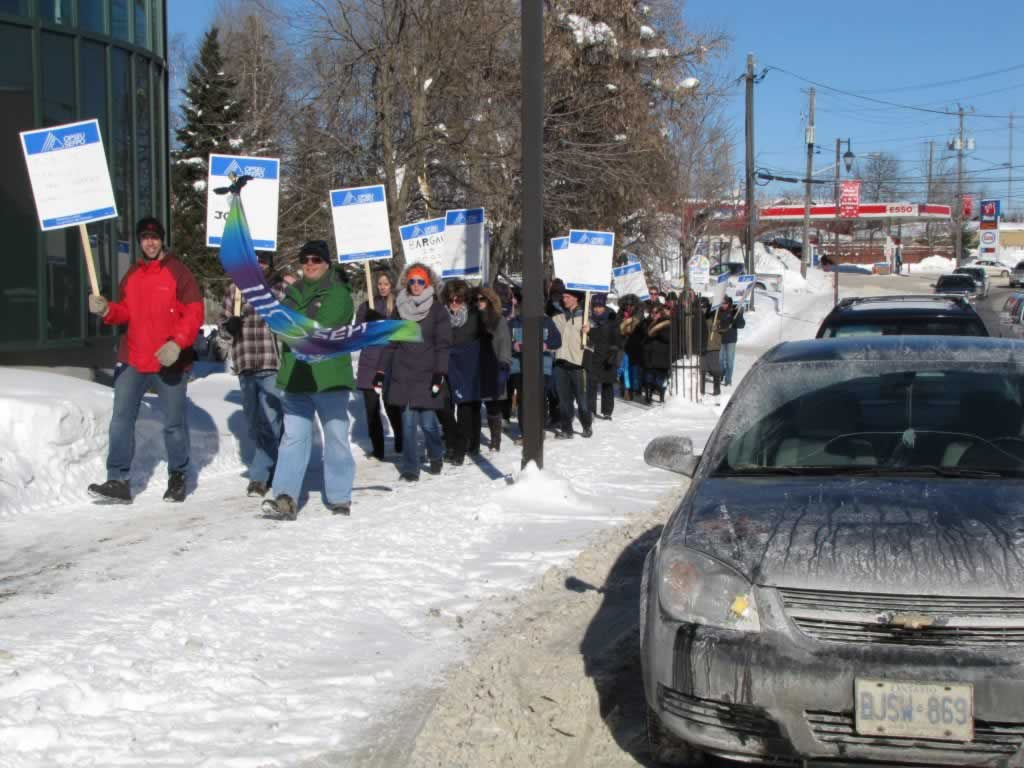 OPSEU members marching in a rally holding up flags and signs