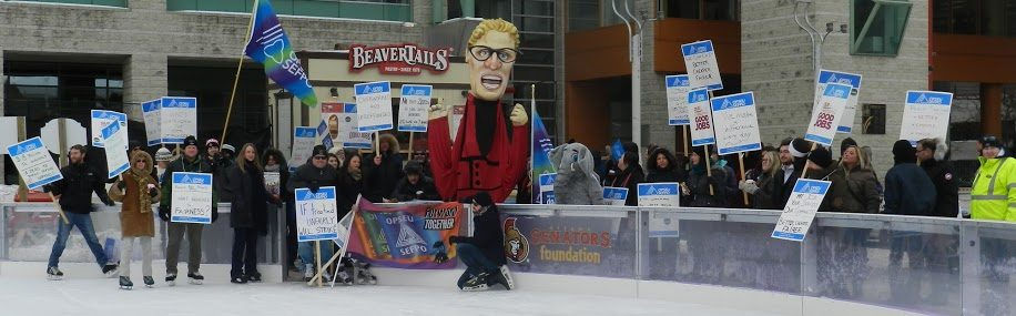 OPSEU members on strike, holding picket signs on ice rink next to Kathleen Wynne puppet