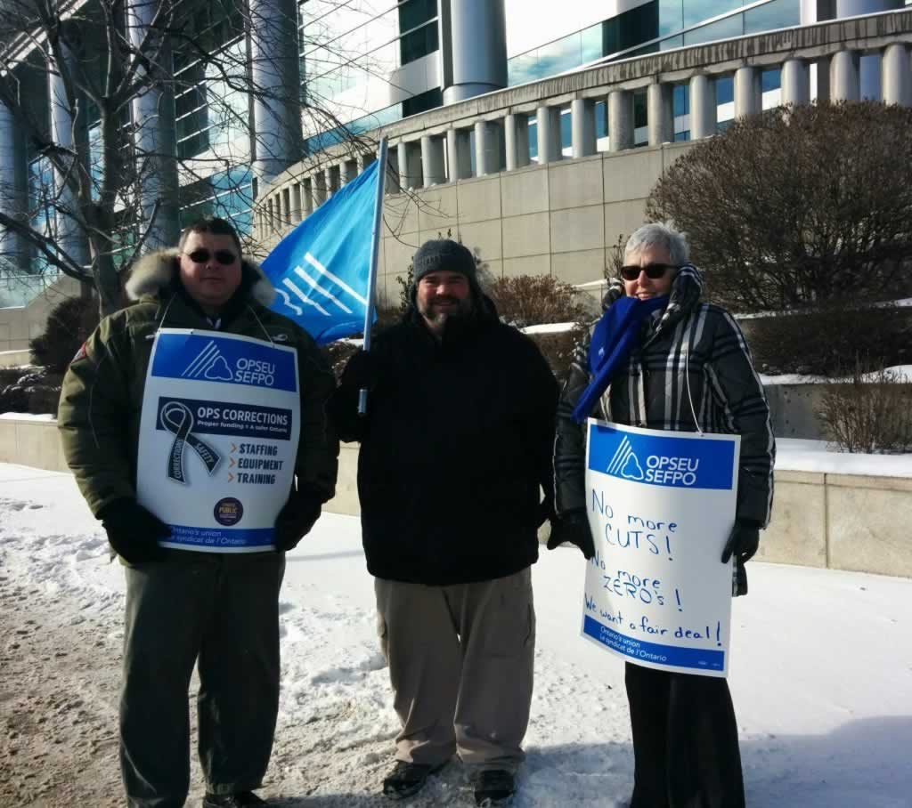OPSEU members holding signs that say OPS corrections and 'No more cuts!' in Thunder Bay