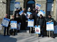 OPSEU members hold up signs as they attend rally in Brockville