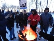 OPSEU members hold up signs and stand around a fire during protest