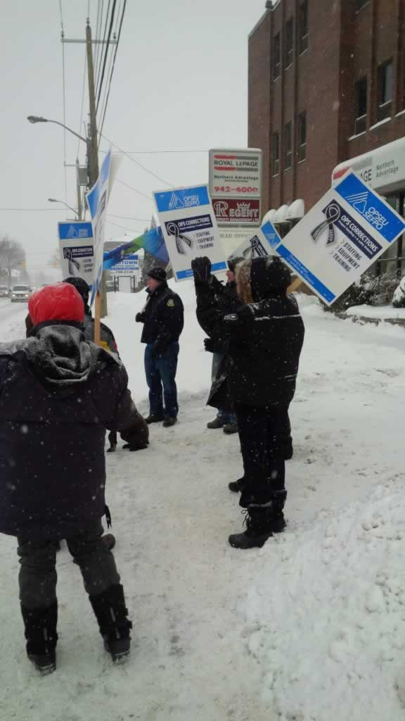OPSEU members hold up signs as they attend rally in Sault Ste Marie