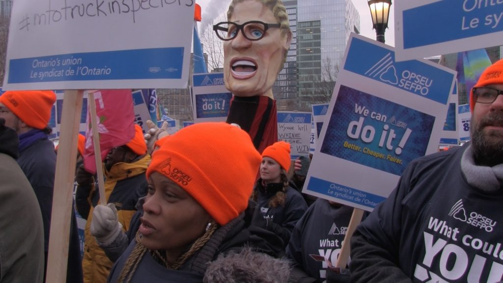 OPSEU members attend rally, holding up signs that say 'We can do it! Better, cheaper, fairer'