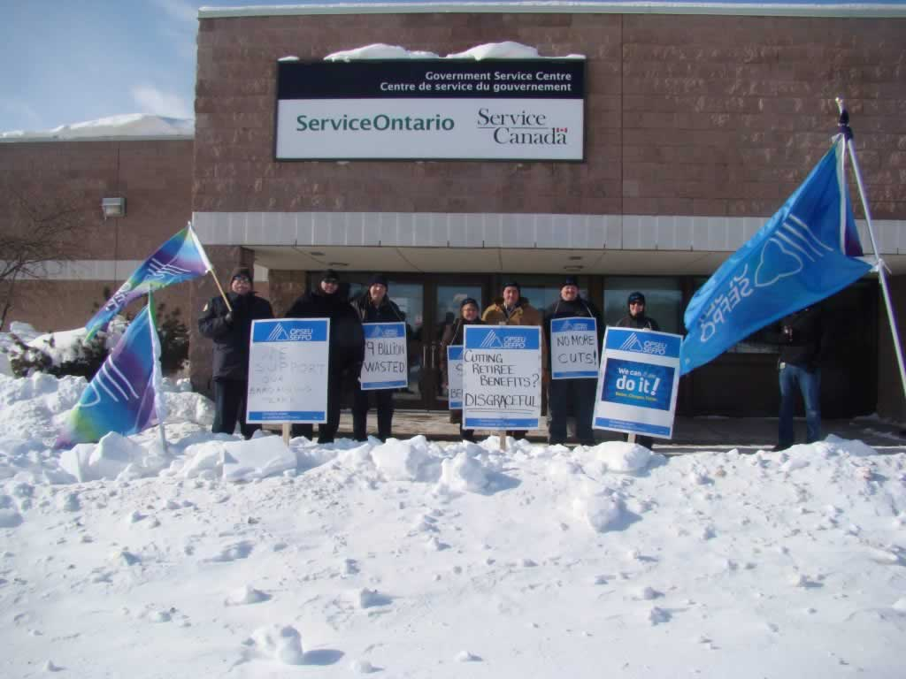 OPSEU members striking in New Liskeard outside of service ontario, holding signs
