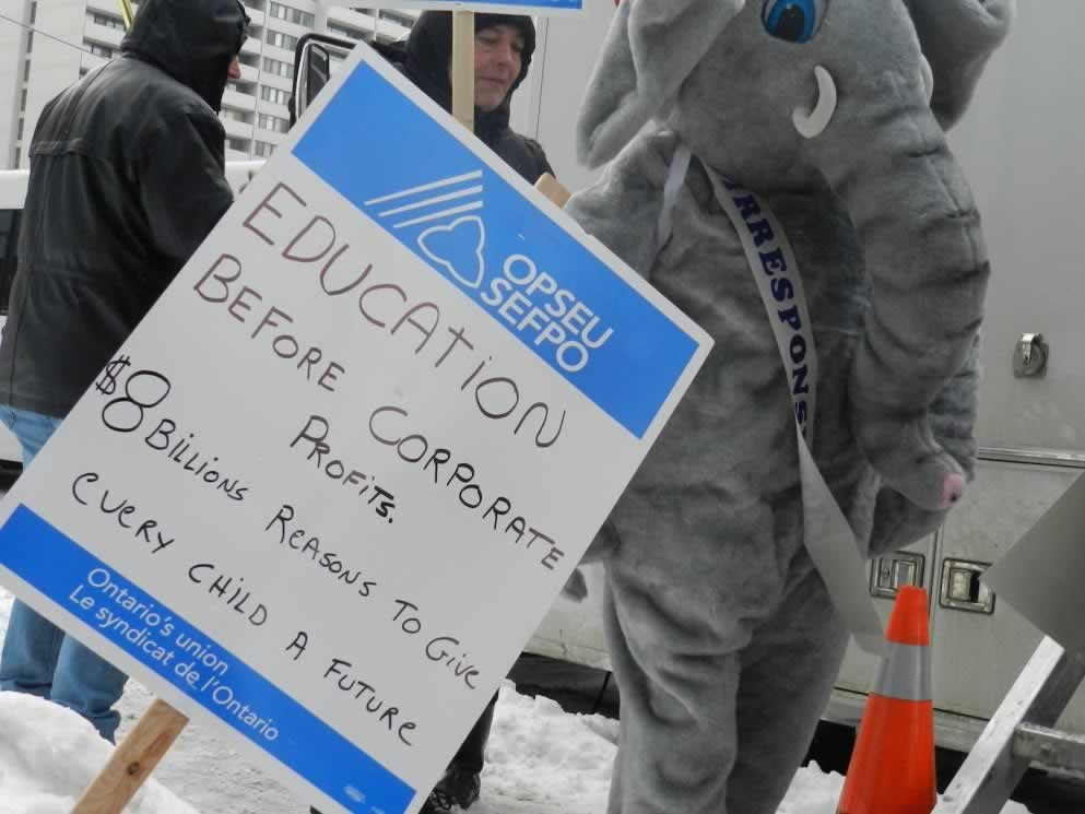 Person in elephant costume standing next to sign that says: Education before corporate profits. $8 billions reasons to give every child a future