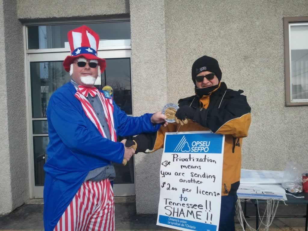 OPSEU member dressed as Uncle Sam shaking someone's hand. Man wearing sign about privatization