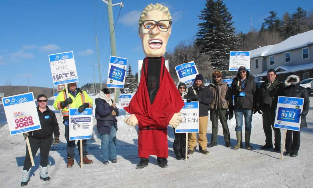OPSEU members pose together holding signs next to Kathleen Wynne