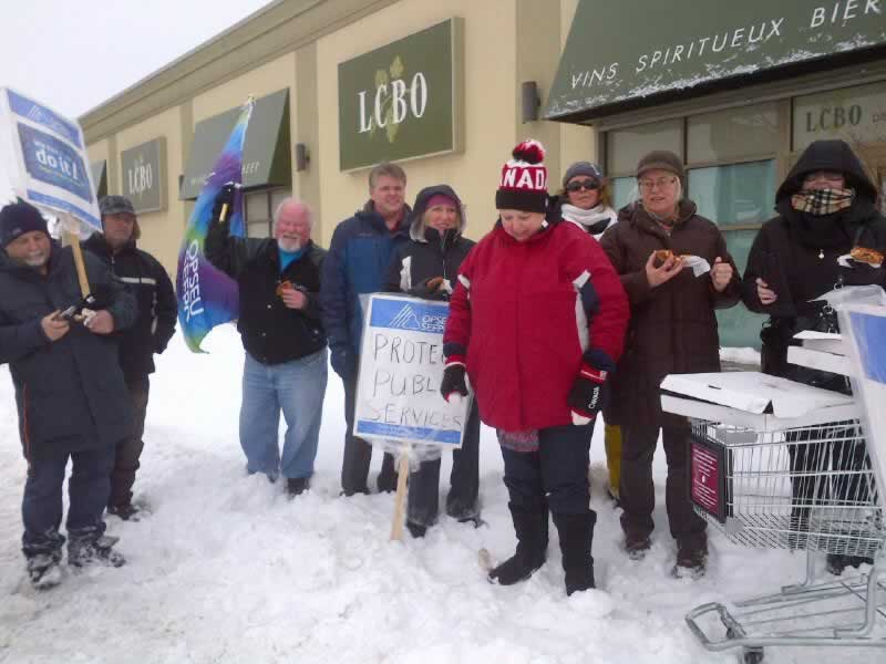 OPSEU members posing together in front of a LCBO, holding an OPSEU flag & signs