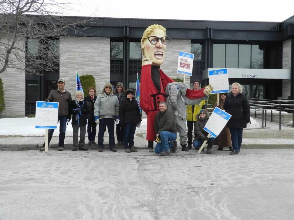 OPSEU members at rally, holding picket signs & next to Kathleen Wynne puppet