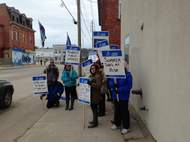 OPSEU members attend rally in Midland, holding signs that says: Summer jobs at risk, protect public services
