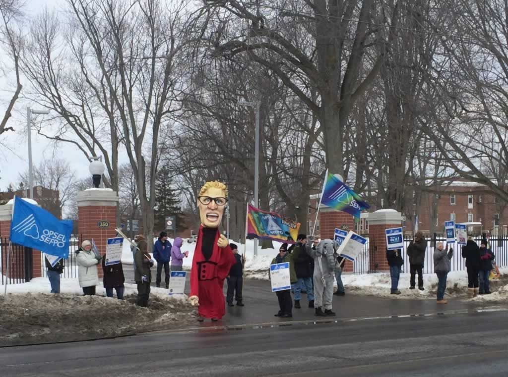 Rally in Belleville. Members are holding OPSEU flags, picket signs & a Kathleen Wynne puppet