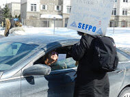 Rally in Ottawa. Member holding picket sign while talking to someone in vehicle