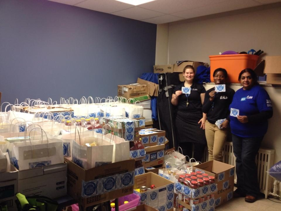 OPS workers posing next to boxes and bags of food for the food drive