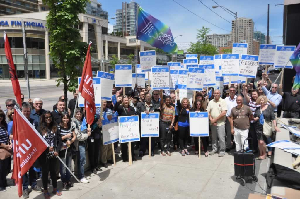 Large group of people holding up flags and signs about respecting unions