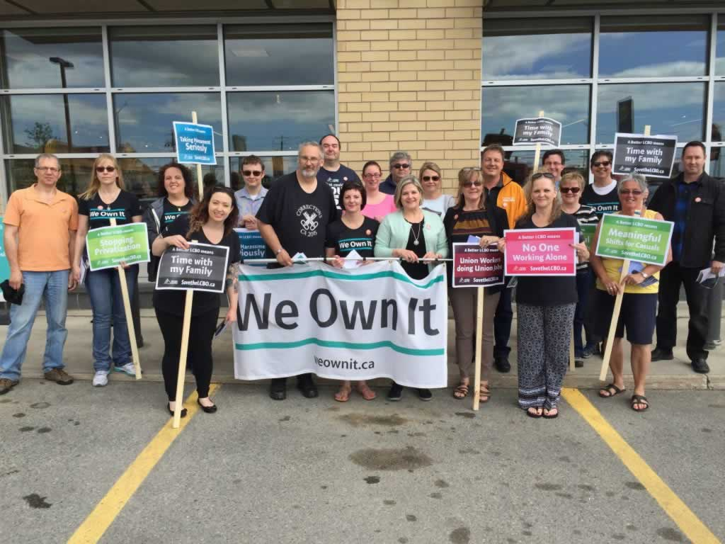 Group of people standing in front of the LCBO with flags and signs