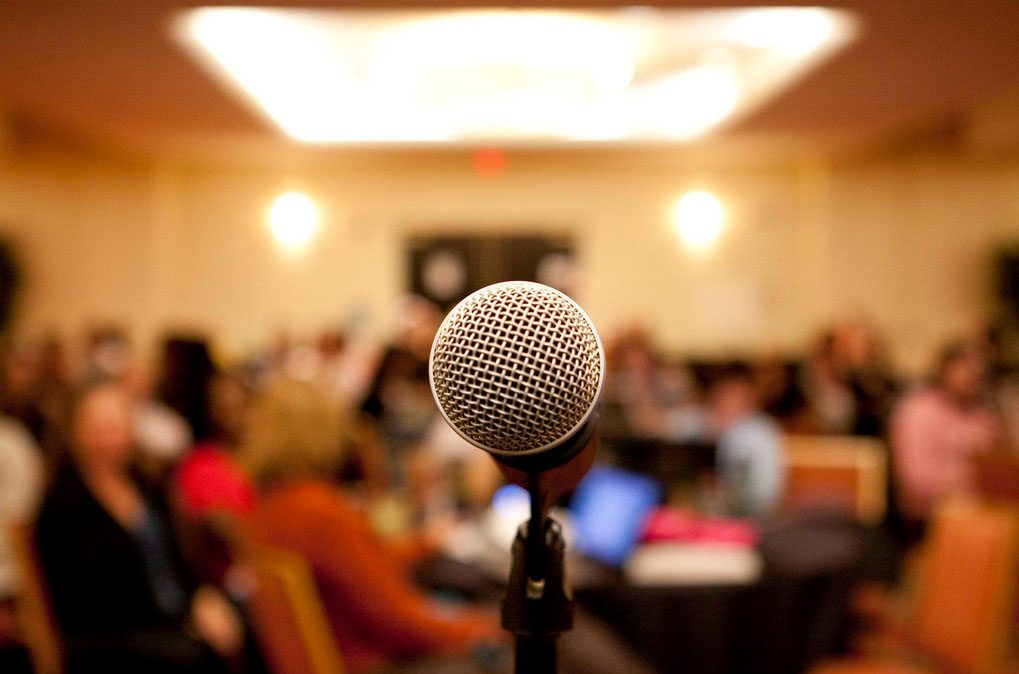 Close-up of a floor mic with a blurred background of a meeting room
