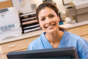 A young smiling woman in blue scrubs sitting in front of a computer
