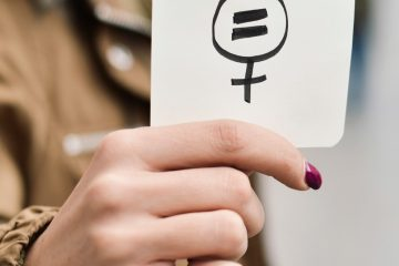 A hand holding up a pay equity symbol drawn on a piece of paper