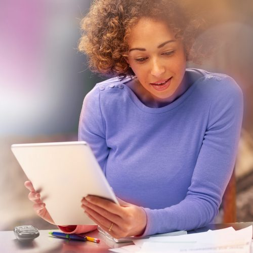 A young Black woman sitting at a desk holding up a notepad and looking down at papers on the desk