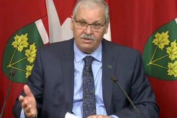 OPSEU President Warren (Smokey) Thomas speaking into a microphone in front of an Ontario flag.