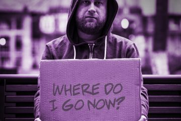"""Homeless person sitting on a bench holding a sign that says """"Where do I go now?"""""""
