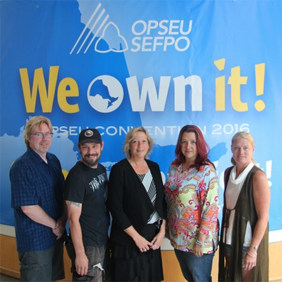 Members of the 2017 LBED Bargaining Team pose in front of an OPSEU We Own It! banner