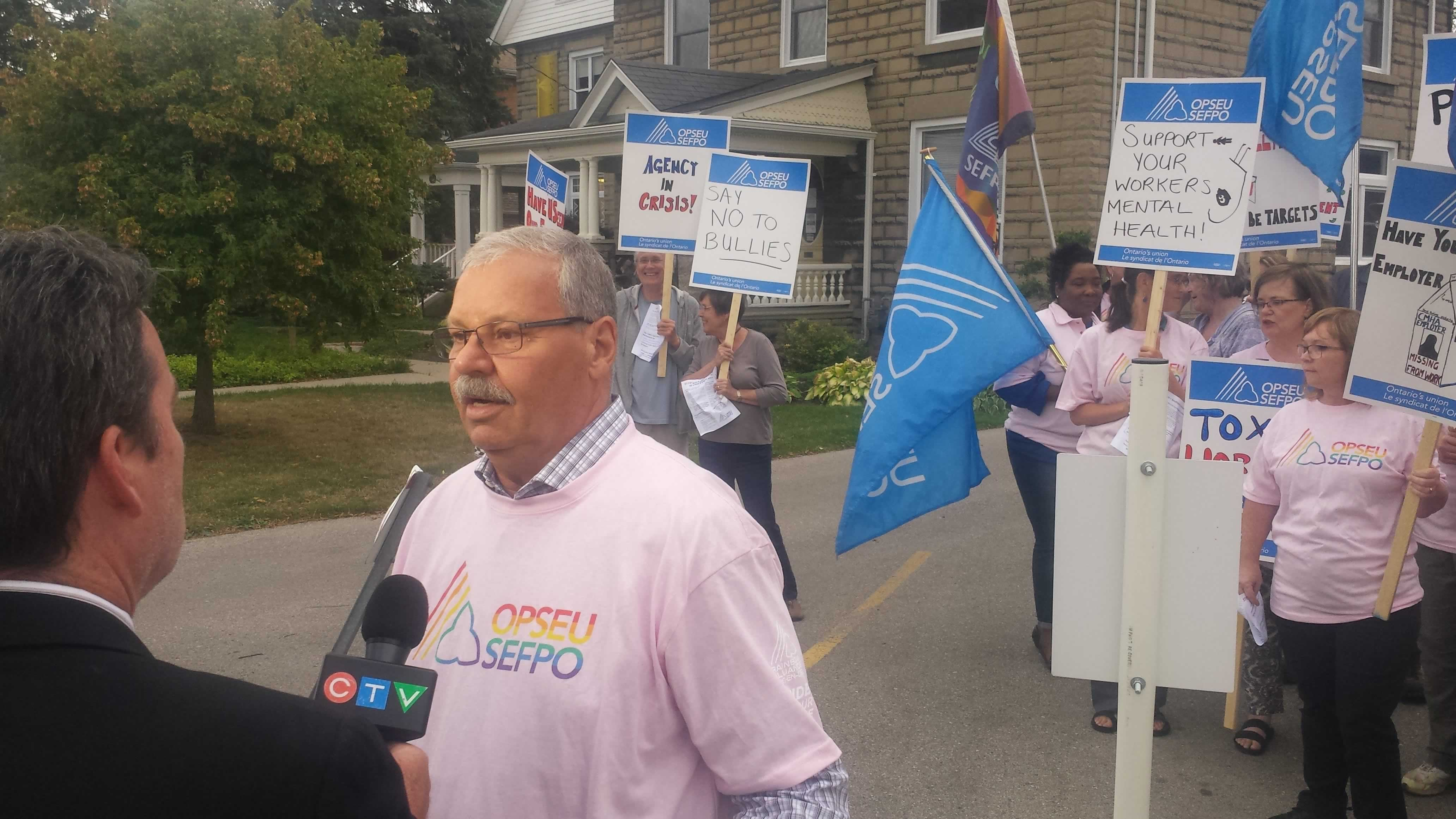 OPSEU President Warren (Smokey) Thomas speaks to reporters during a rally in Elgin