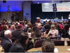 Large group of OPSEU members sitting at tables on the Convention floor.