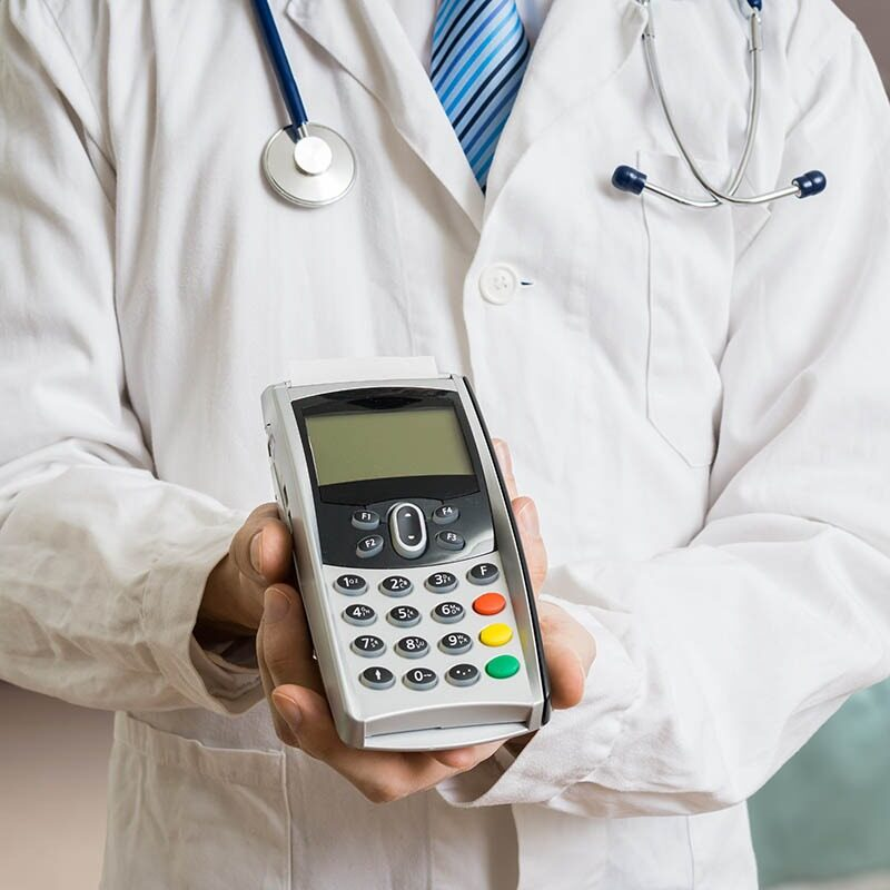 Hospital professional in white coat holding a credit card machine
