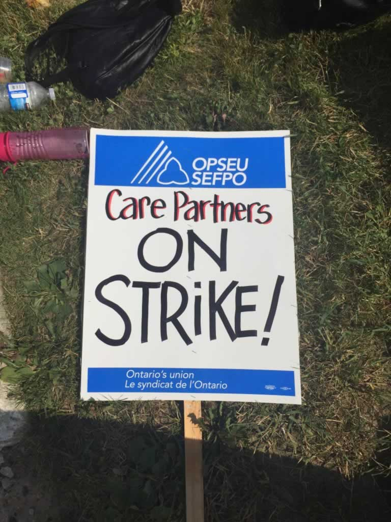 """OPSEU """"Care Partners On Strike!"""" picket sign."""