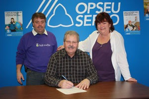 """OPSEU President Warren (Smokey) Thomas signs the """"Take a Stand"""" pledge with two other OPSEU members."""