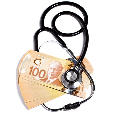 Stethoscope on stack of Canadian bank notes
