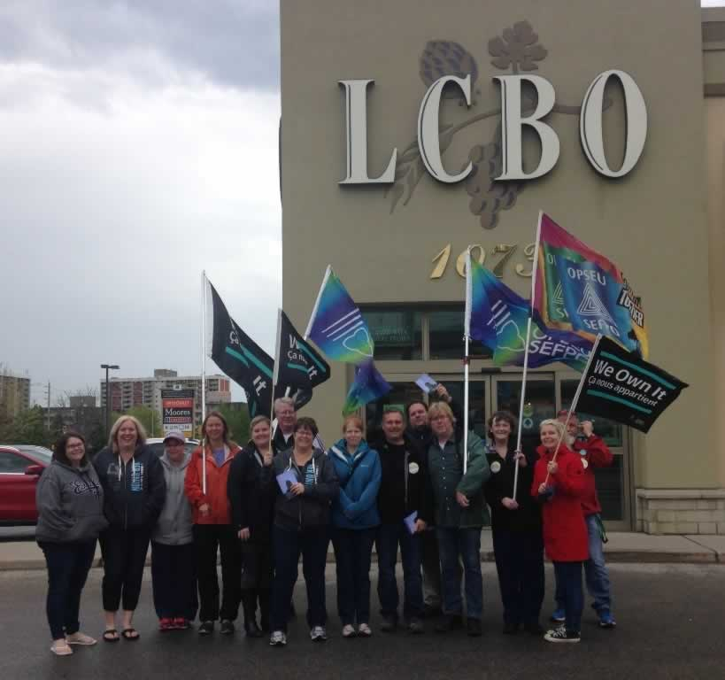 OPSEU members hold flags during a rally outside and LCBO in London.