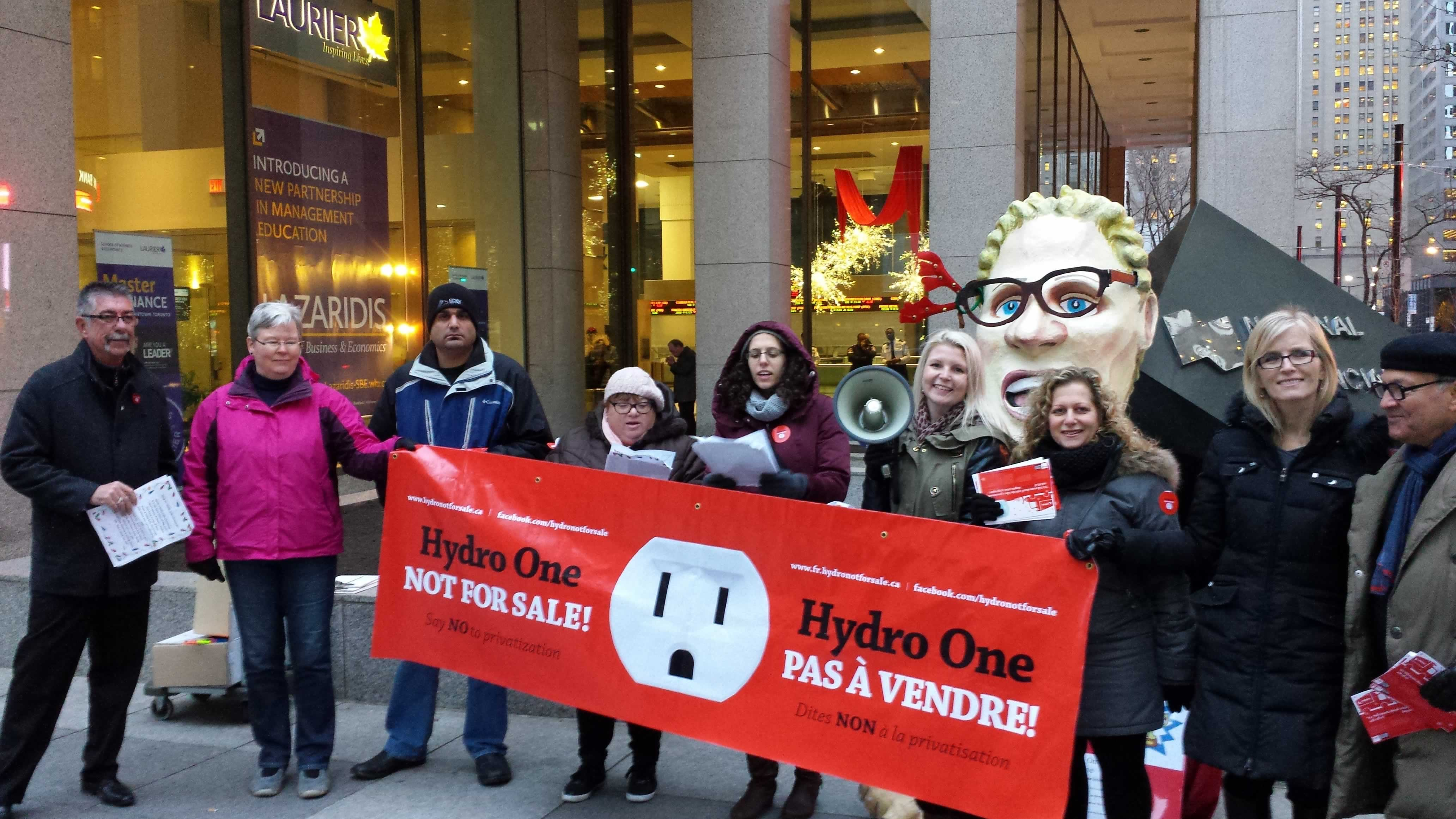 """OPSEU and OFL members hold a """"Hydro One Not for Sale"""" banner during a rally."""