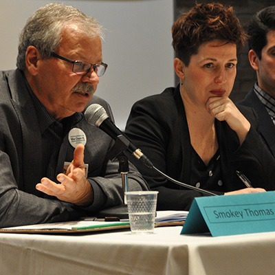 OPSEU President Warren (Smokey) Thomas speaking into a microphone during the We Own It Town Hall in Kingston