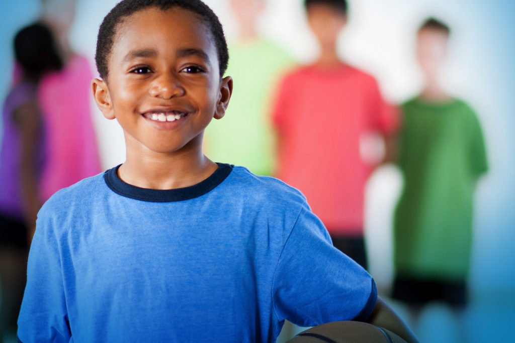 Young boy in a blue shirt smiles as (faded) children look on behind