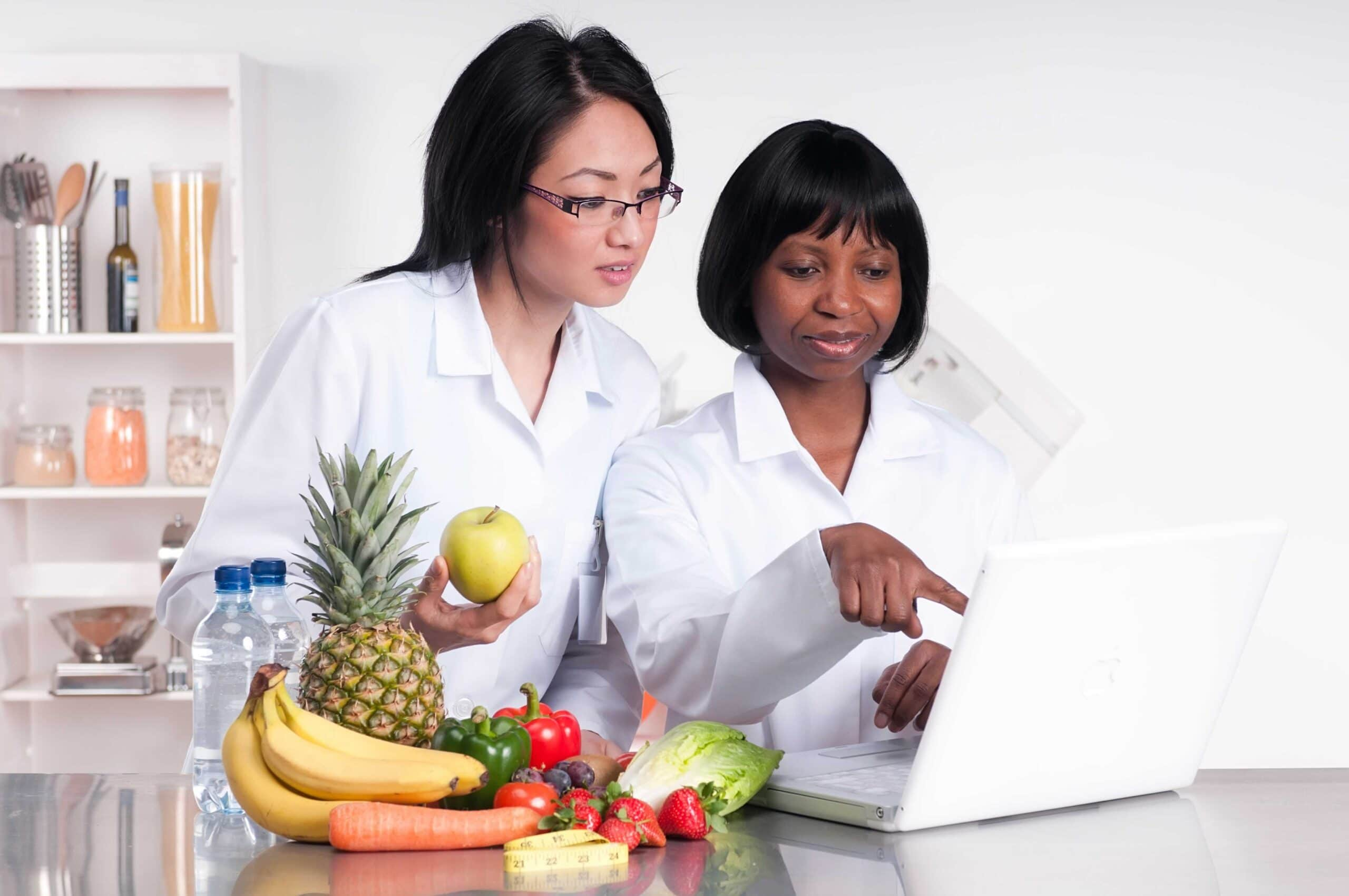 Dietitians discussing some information on a laptop with a pile of fruit and vegetables next to them.