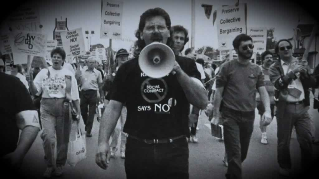 black and white image of protest, people with rally signs, Smokey Thomas with a megaphone